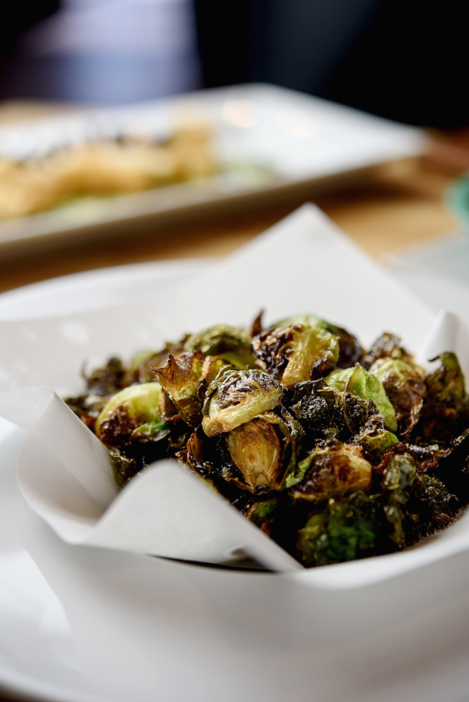 Charred and crispy Brussels sprouts are paired with a tangy chili sauce for a surprising appetizer.