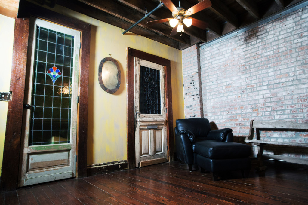 The living room is characterized by weathered wood flooring and exposed brick walls and ceiling beams. An old church pew provides seating.
