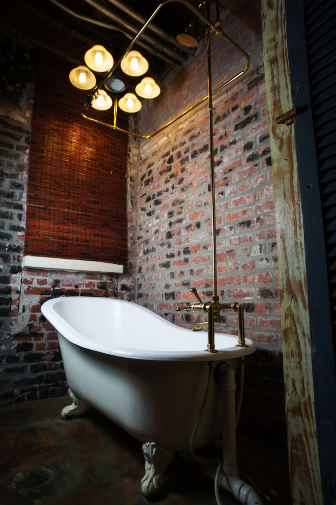 The guest bathroom features a clawfoot tub with a brass faucet and shower enclosure.