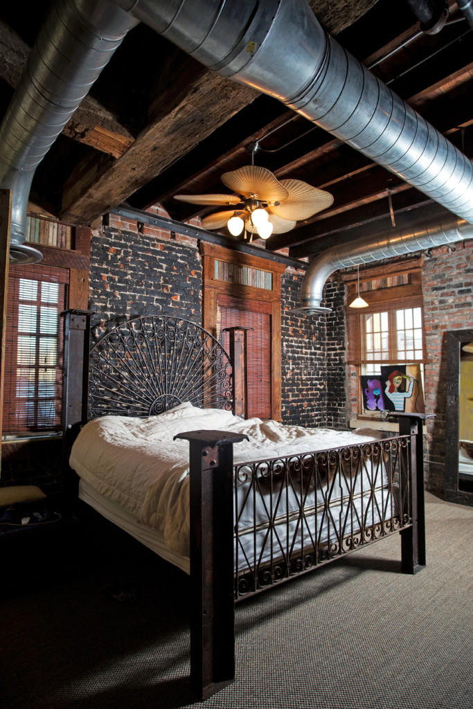 An iron bed frame and headboard align perfectly with the apartment's industrial feel. The exposed brick wall was partially painted black for a charred look.