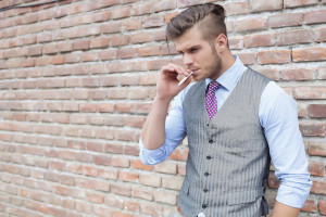 casual young man standing next to a brick wall with a cigarette in his mouth