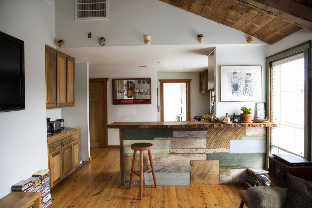 Looking into the kitchen, the breakfast bar makes a statement with its eclectic mix of salvaged wood. The tiny figurines hanging near the ceiling are from England and were passed down to Taylor by her grandmother.