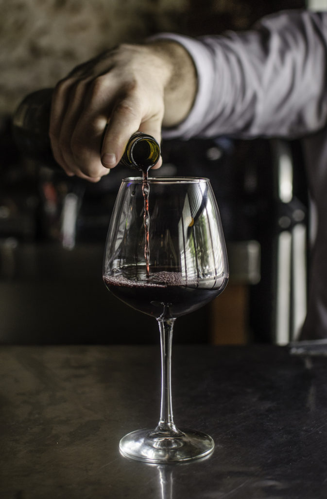 A bartender pours a glass of red wine at the River Room.