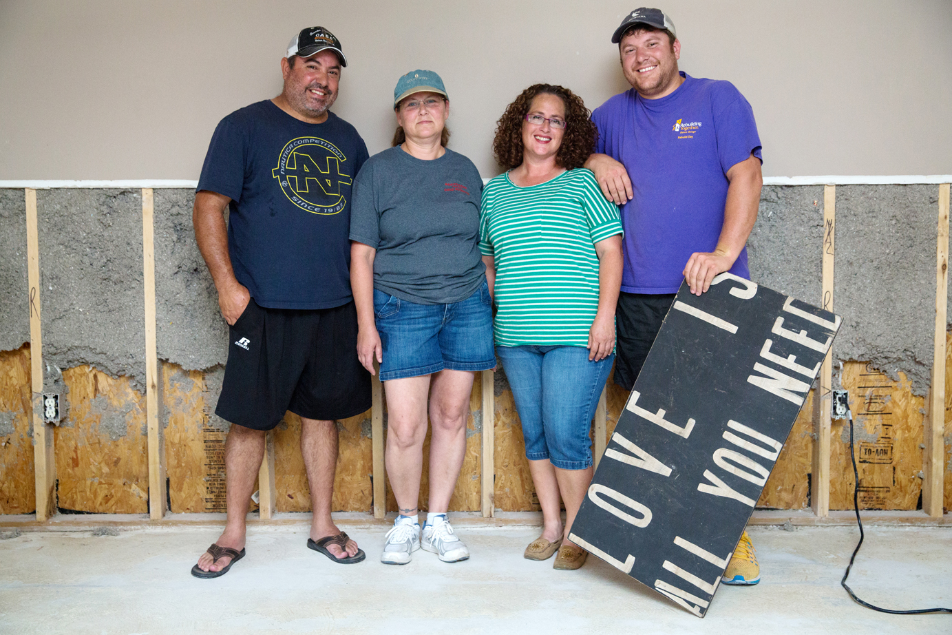 Keith Martine, Mary Jones, Amy Daigle and Dustin Clouatre stand in Jones' now-gutted home, where Jones and Daigle were rescued from floodwaters. Photo by David Morris.