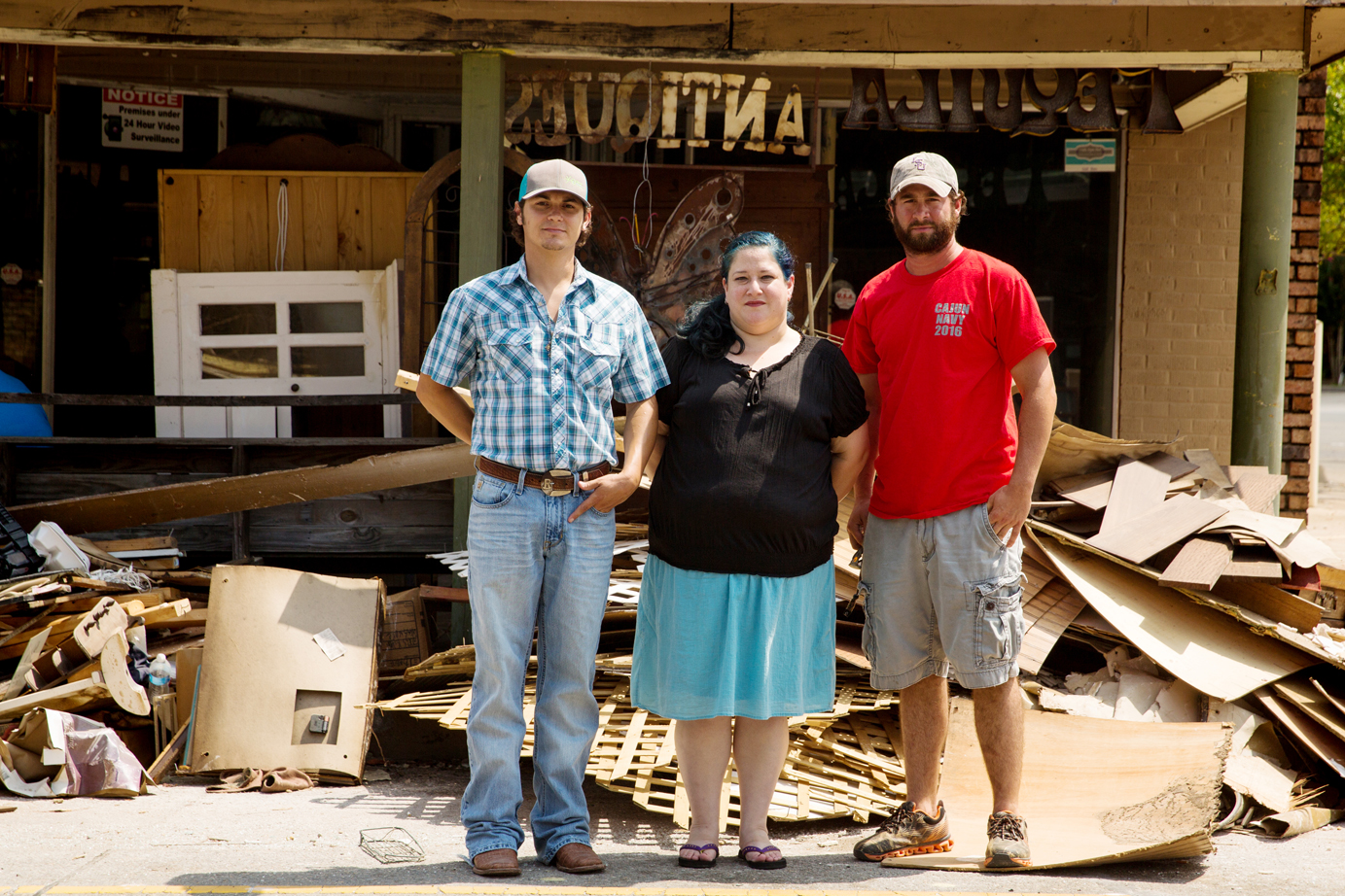 Nick Ramos, Lyndy Donaldson and Brandon Burchfield reunite in the remains of the Denham Springs Antique Village, steps from where Burchfield tied his boat after rescuing Donaldson when several feet of water engulfed this street in August. Photo by David Morris.