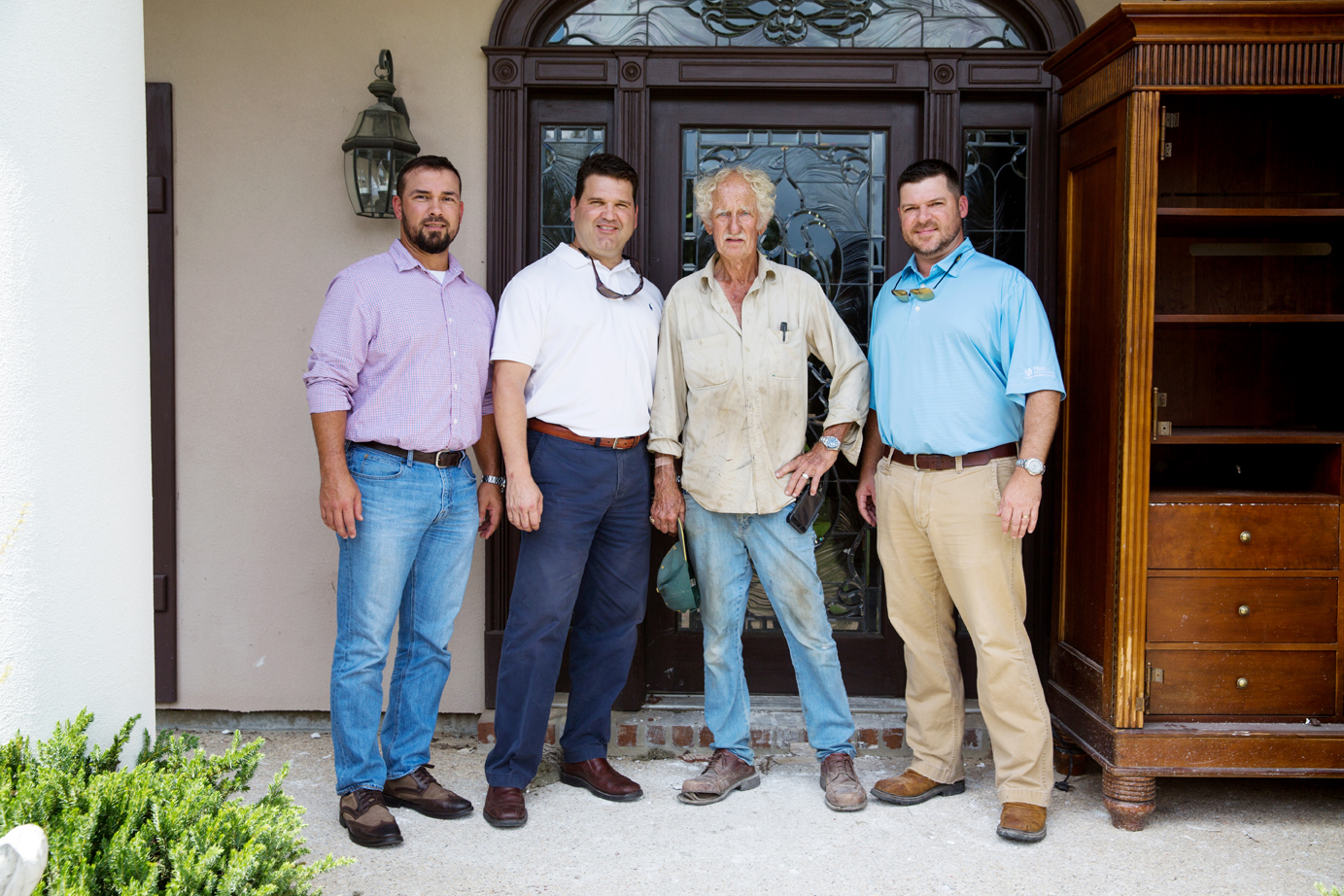 Brian Bordelon, Chad Chenevert, Newell Prater and Calvin Foreman revisit Prater's home in Centurion Place, which took on several feet of water. Photo by Davis Morris.