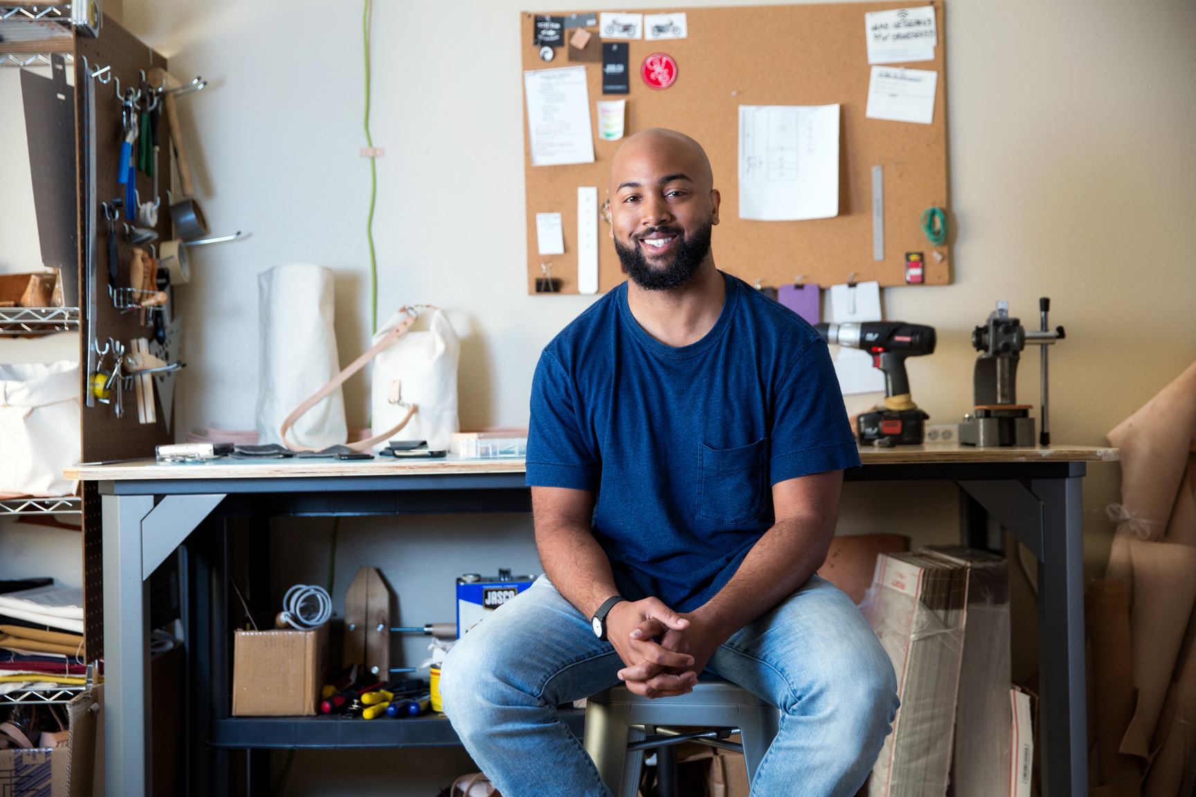 In his home workshop in the Garden District, Damien Mitchell sketches designs and fabricates leather wallets, bags, pouches and accents from scratch. He gets around the area on foot or his motorcycle. Photo by Collin Richie.