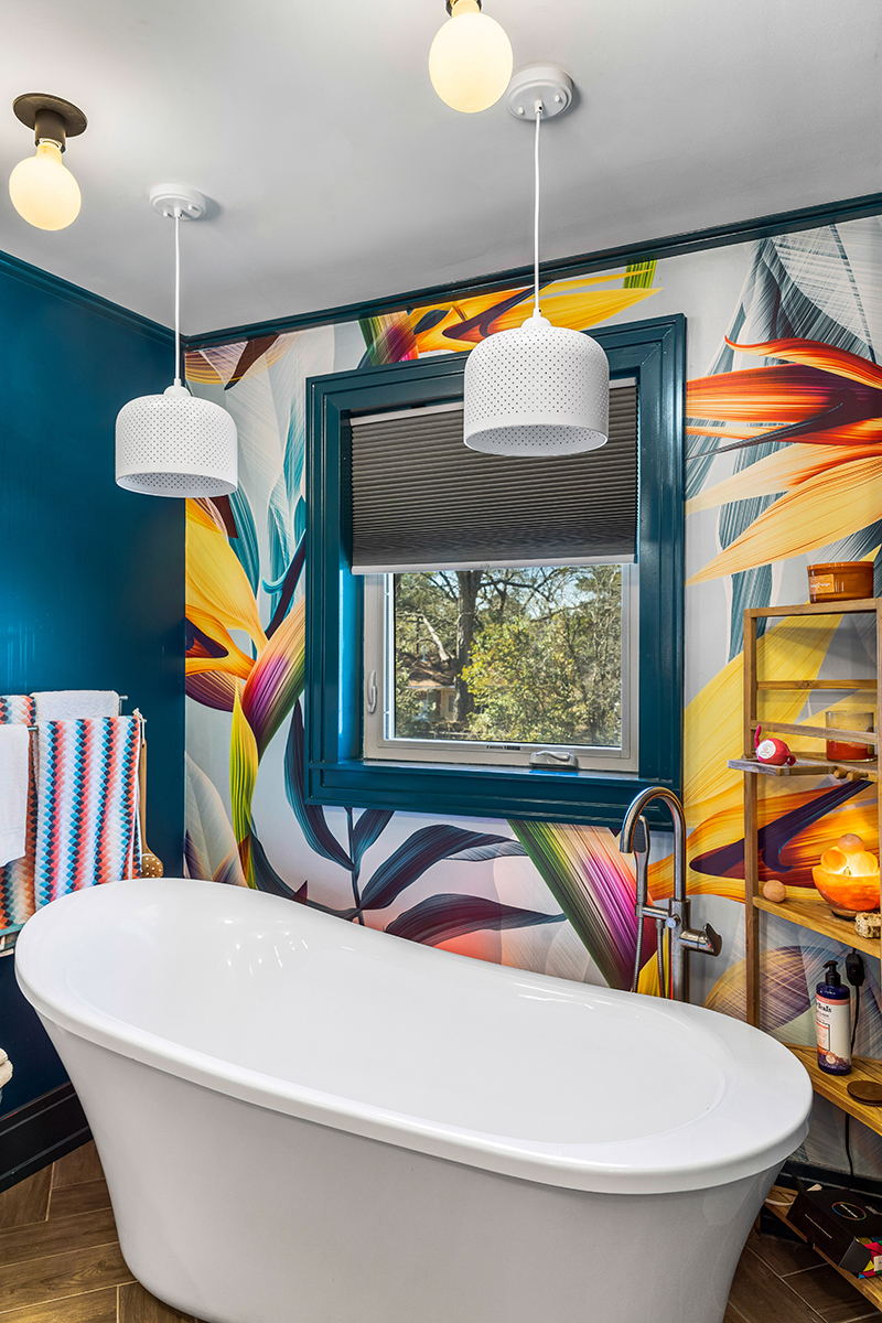 Colorful bathroom highlighting bathtub with birds of paradise wallpaper and teal paint on window trim