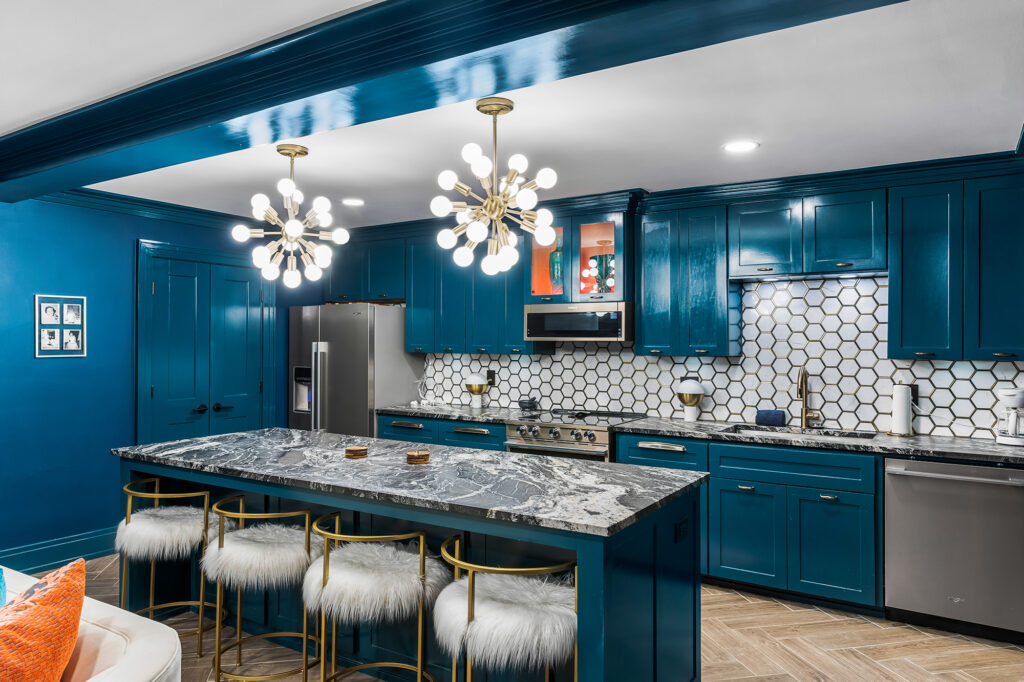 Colorful kitchen with high gloss teal cabinets and center island. Mid century light pendants
