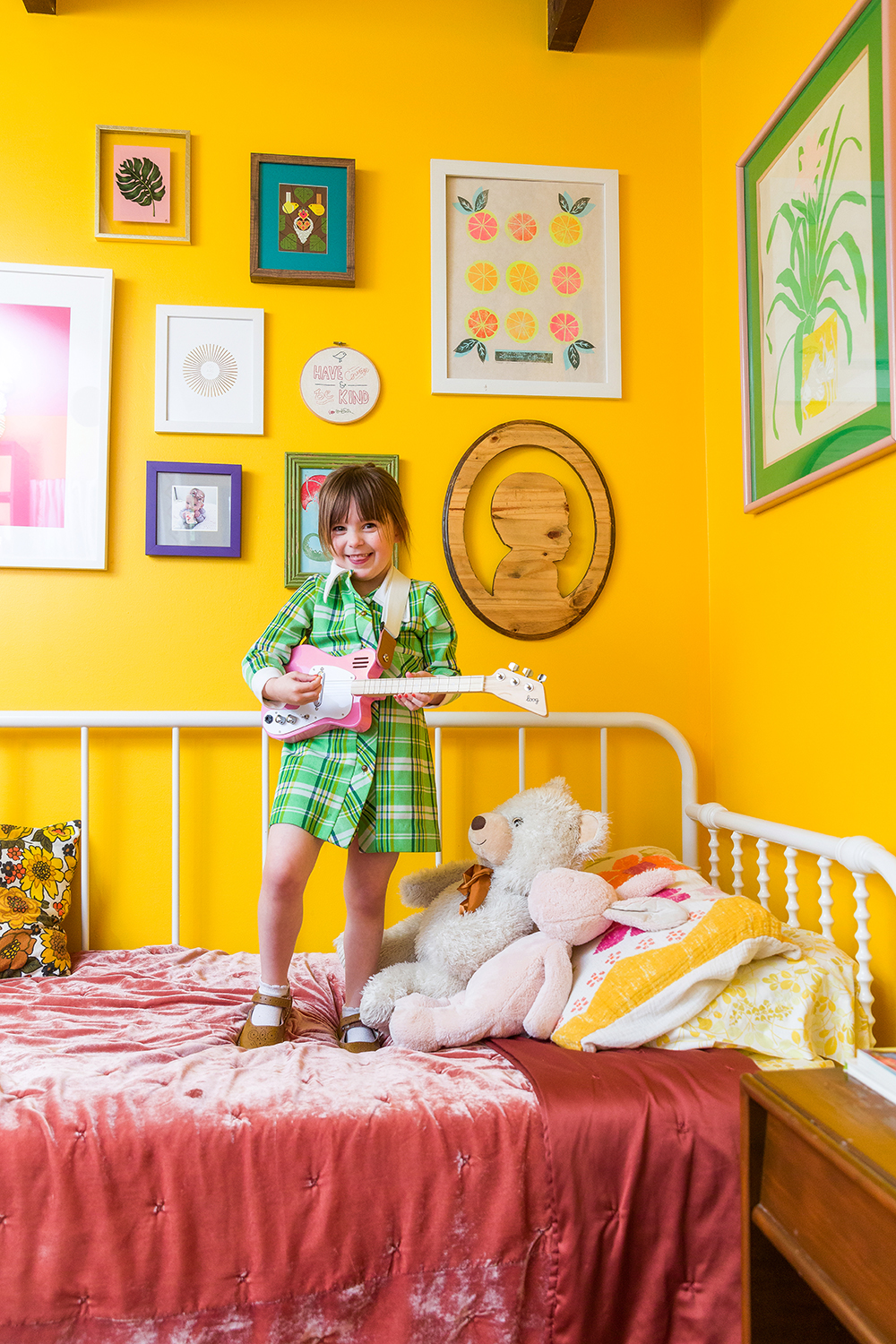 Alice Daniel in colorful green plaid dress stands on her bed playing pink kid's guitar