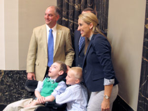 Gov John Bel Edwards takes photos with medical marijuana supporter Katie Corkern, right, whose son Connor, center in the wheelchair, has a rare brain disorder that causes uncontrollable seizures, on Thursday, May 19, 2106, in Baton Rouge, La., after Edwards signed a bill to expand and jump-start Louisiana's medical marijuana program. (AP Photo/Melinda Deslatte)