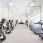 A wall of windows open to a courtyard which provides bright, natural light to the cardio room at Future Fitness.
