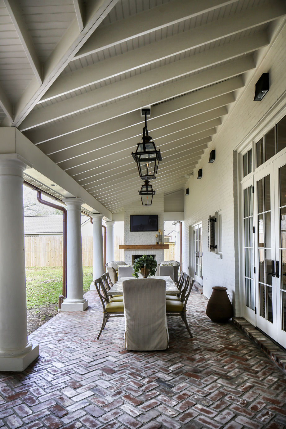 This deep L-shaped back porch was added as part of a renovation. Custom  Bevolo lanterns illuminate dining and seating areas. Design by Anne  McCanless.