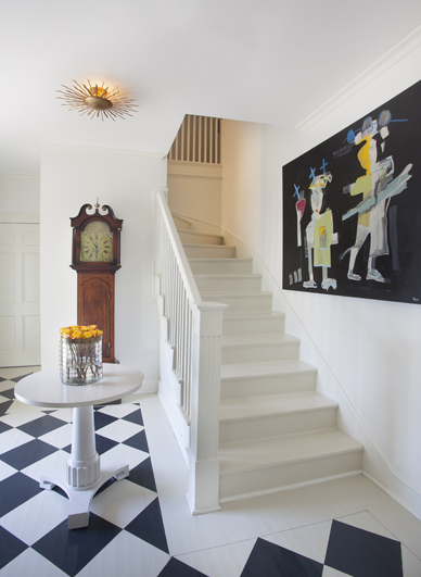 """Artist Sally Conklin painted the black and white design on the foyer's hardwood floor. A vibrant Tony Mose painting hangs along the stair wall. """"I wanted visitors to get a sense of what was to unfold in the rest of the house, so the foyer—which is quite small—was a small gesture,"""" says Larkins."""