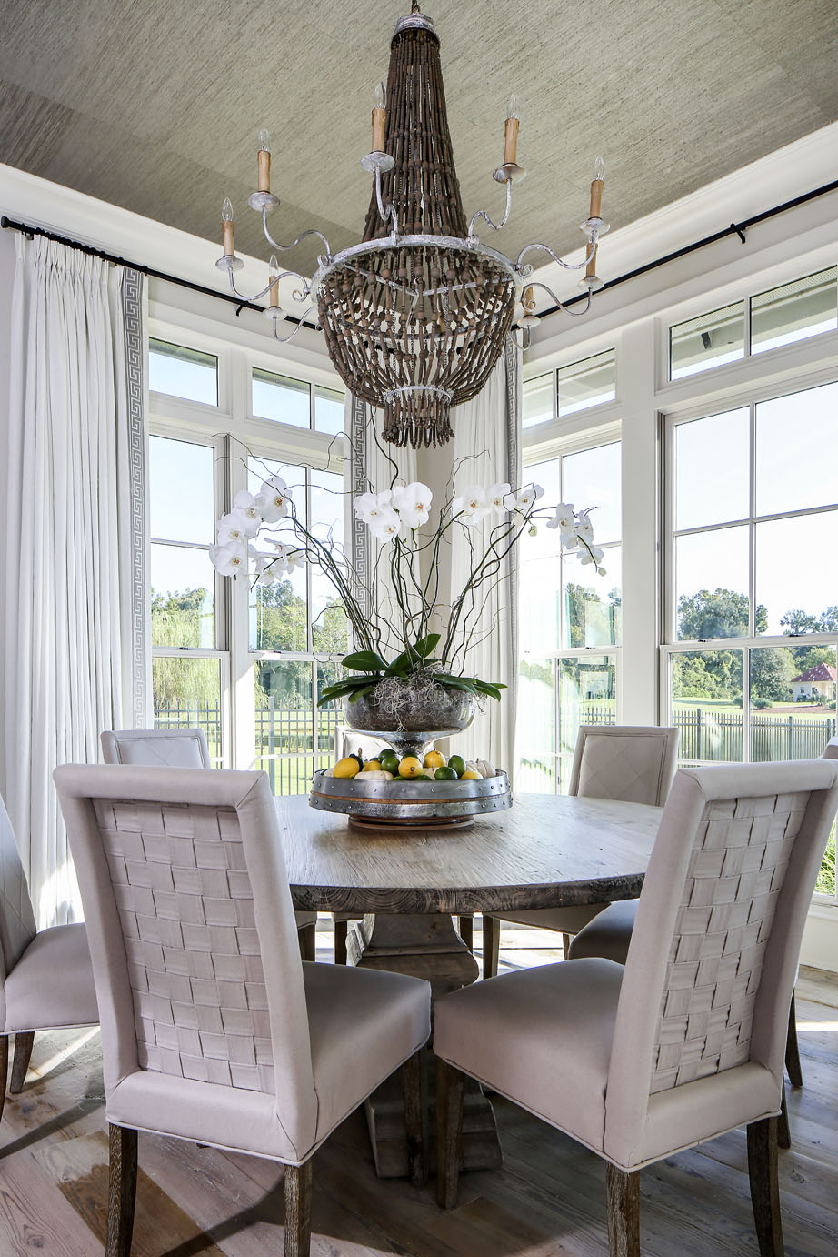 The round dining table and woven-back chairs are from Dixon Smith Interiors.