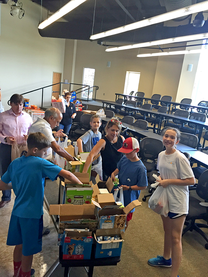 Volunteers of all ages showed up at LCI to help create food bags for flood victims. Photo by Jeannie Frey Rhodes.