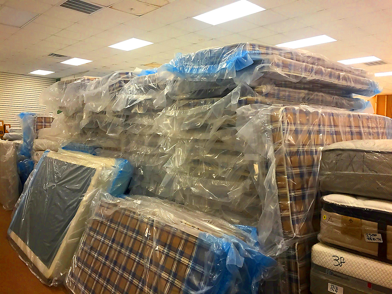 New mattresses purchased at an extreme discount with donations were lined up ready to be delivered to families who lost everything in the flood. Only $65 buys a new mattress for those in need. Photo by Jeannie Frey Rhodes.