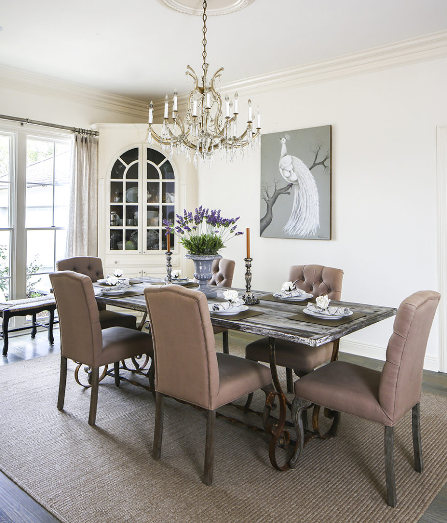 """Benjamin Moore's """"White Dove"""" creates a pristine palette on walls in the dining room and throughout the home's public spaces. Built-in corner cabinets provide a perfect spot for Jan to store and display the treasures she finds at thrift shops and garage sales."""