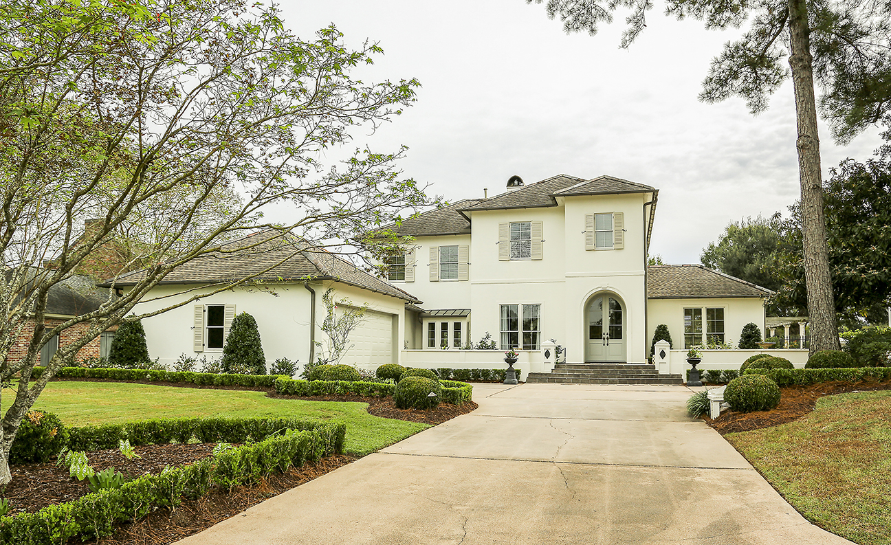 """When the Ponsons purchased this home, one of their first moves was to repaint the exterior, once a """"brownish plum color,"""" as John says, in a quiet cream hue. They also added all new landscaping."""